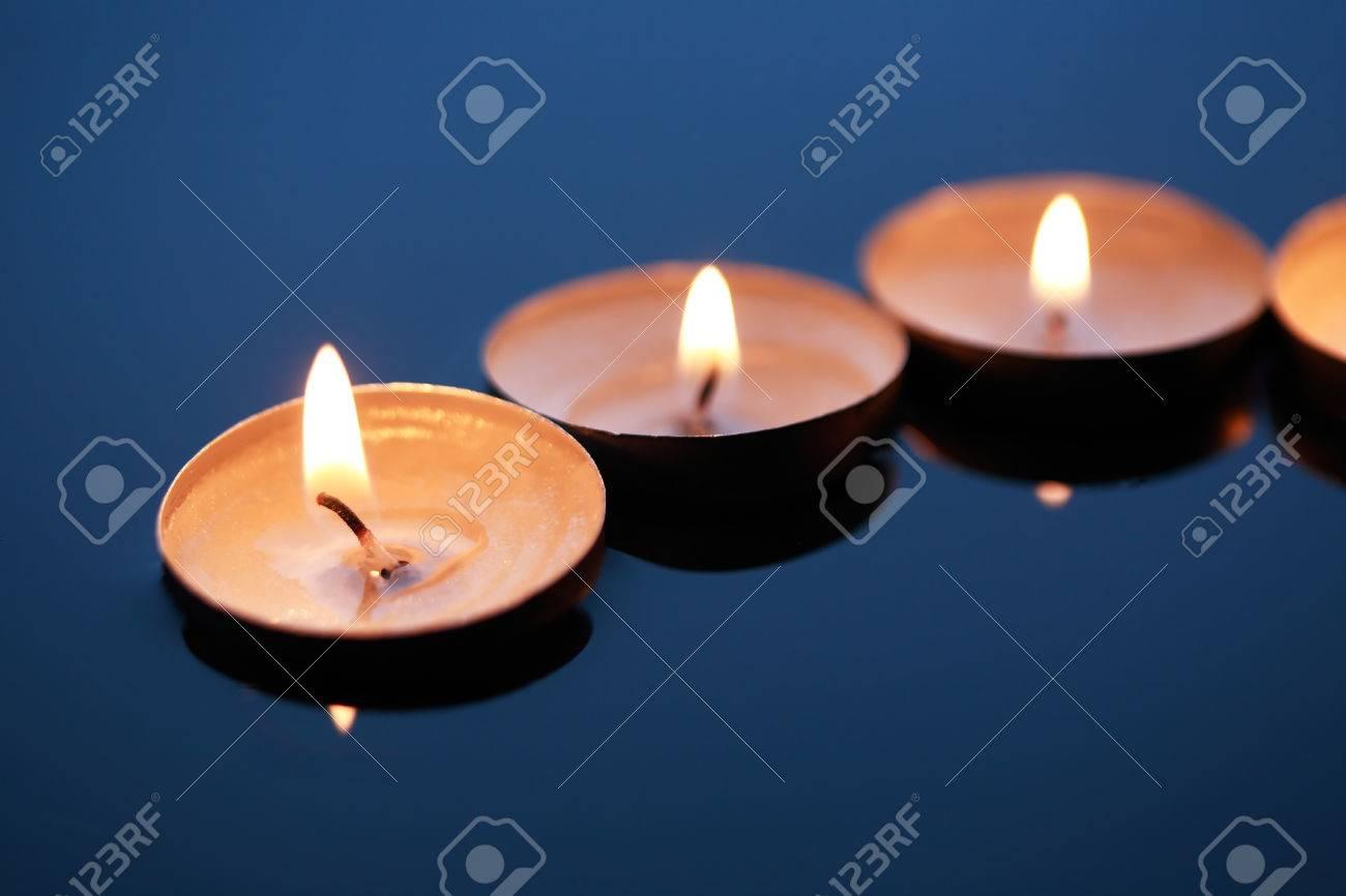foto de archivo pocas encender velas en la superficie del agua de color azul oscuro