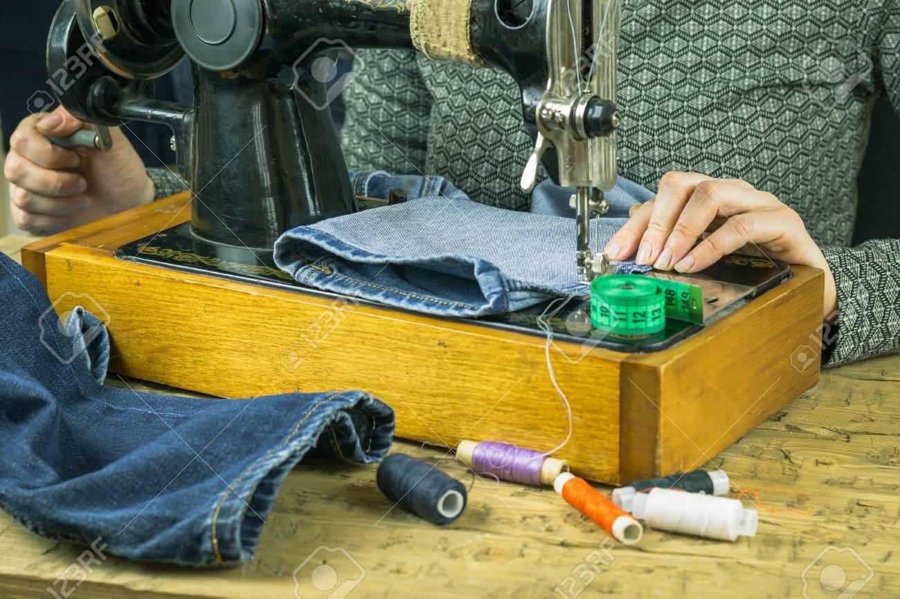 Une femme cousant des jeans sur le manuel de la machine à coudre. Le  concept de production à domicile et de réparation de vêtements.
