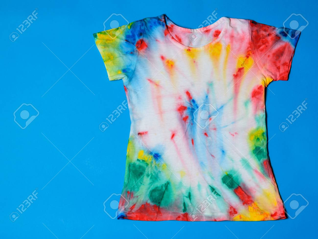 4a00dcfc Stock Photo - T-shirt painted in tie dye style on a blue background. White  clothes painted by hand. Flat lay. Place for text.