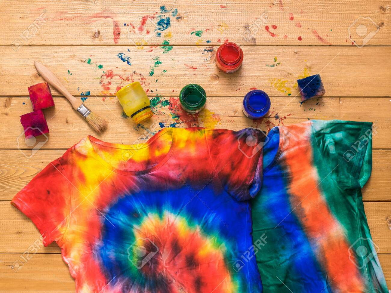 The process of painting a t-shirt in the style of tie dye in the form of a spiral. White clothes painted by hand. Flat lay. - 150148182