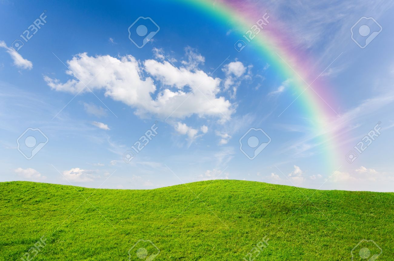 green grass with blue sky and rainbow as background stock photo