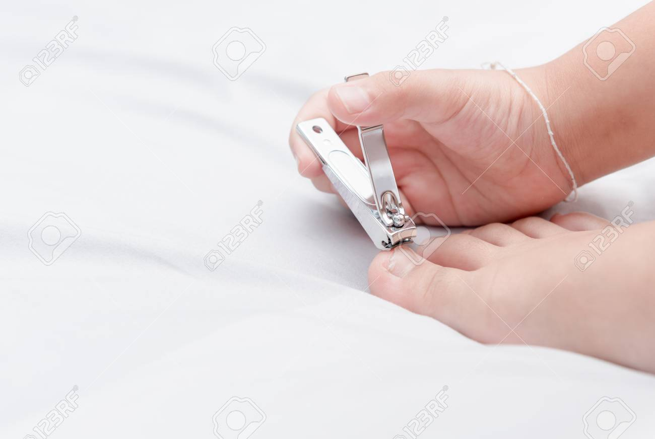 Girl Kid Cutting Toenail By Nail Clippers, Healthy Care Concept ...