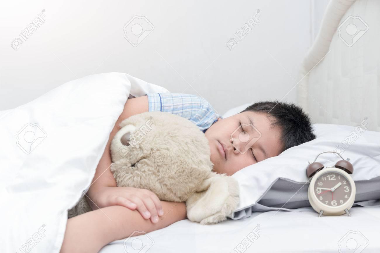 Obese fat boy sleep and hug teddy bear on bed healthy concept stock photo
