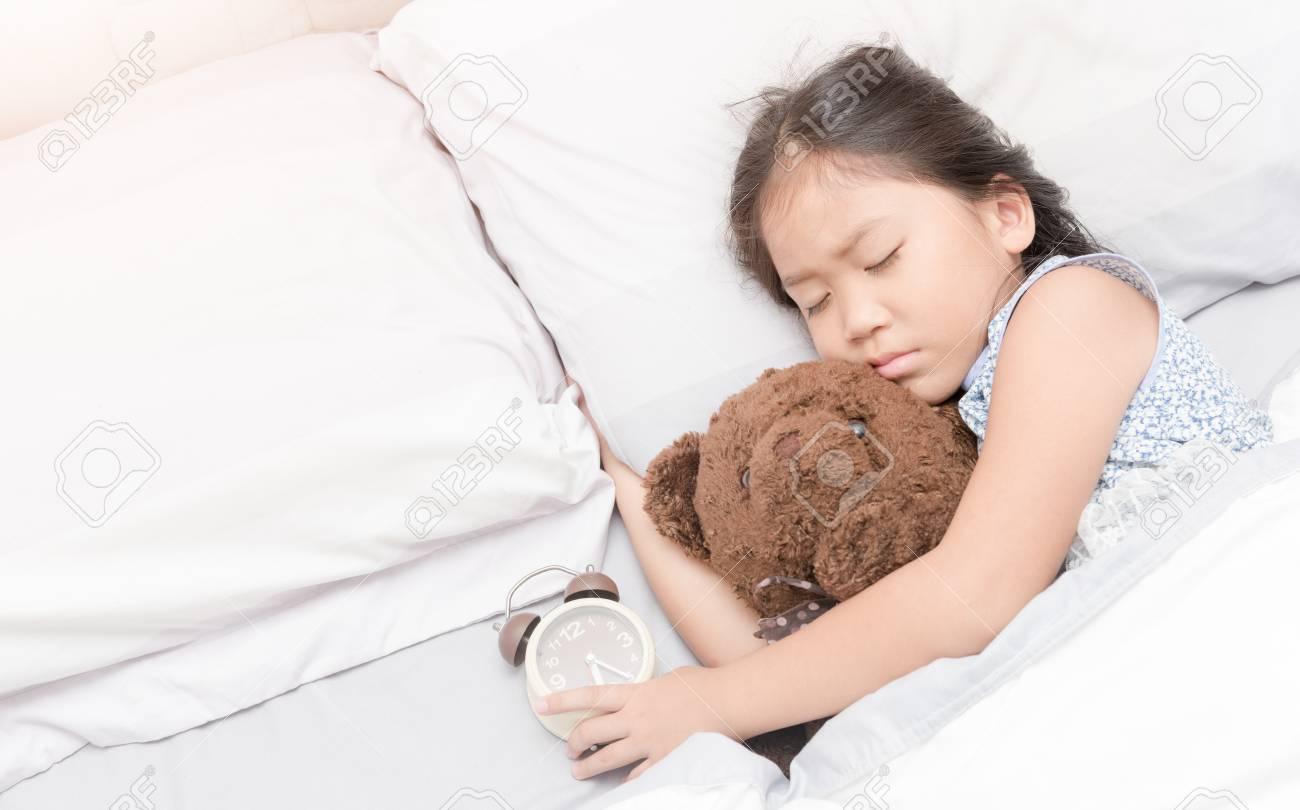 cute little asian girl sleep and hug teddy bear on bed in the bedroom Stock  Photo