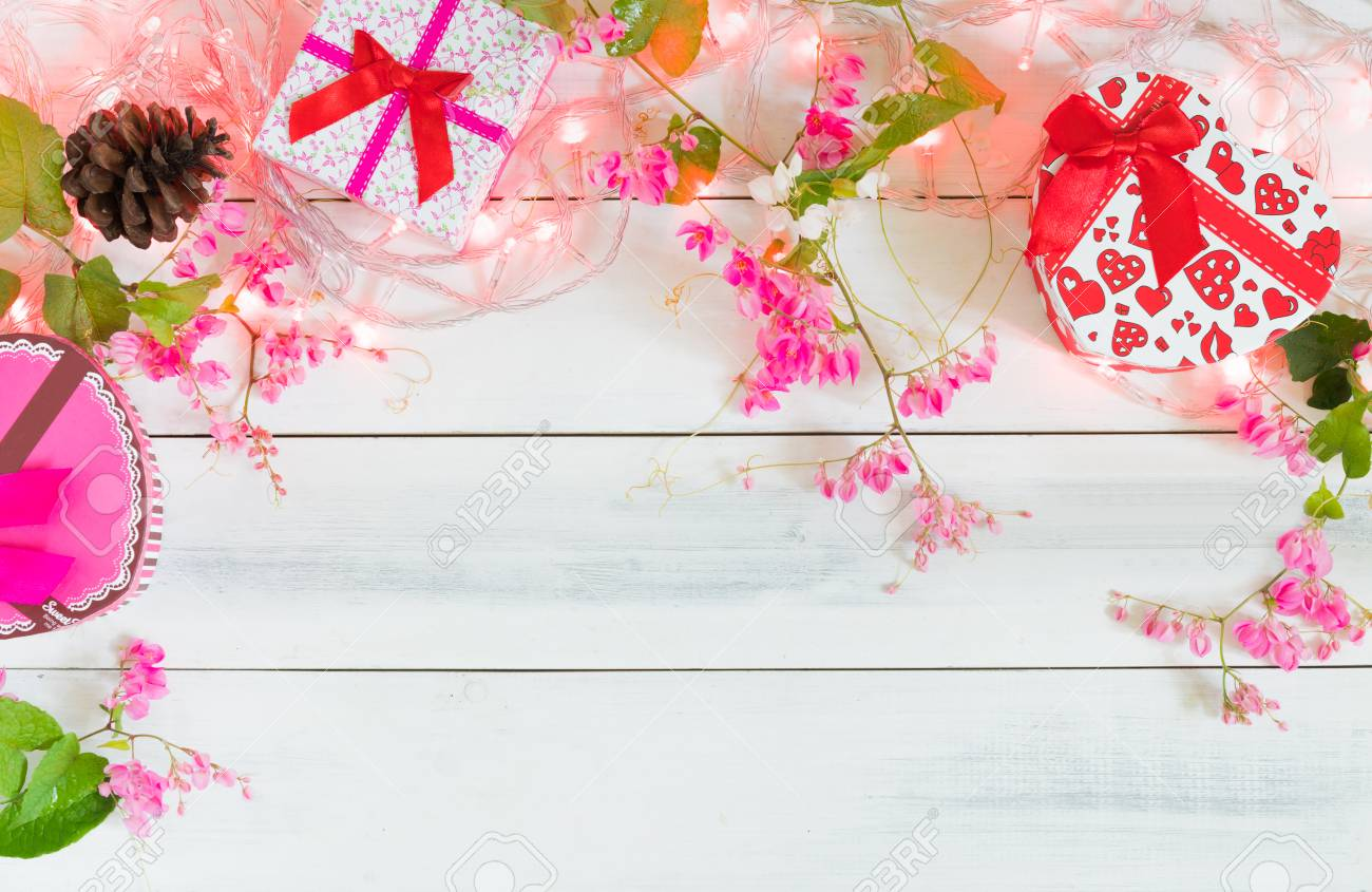 Christmas Lights With Gift Box And Pink Flower On White Wood Stock