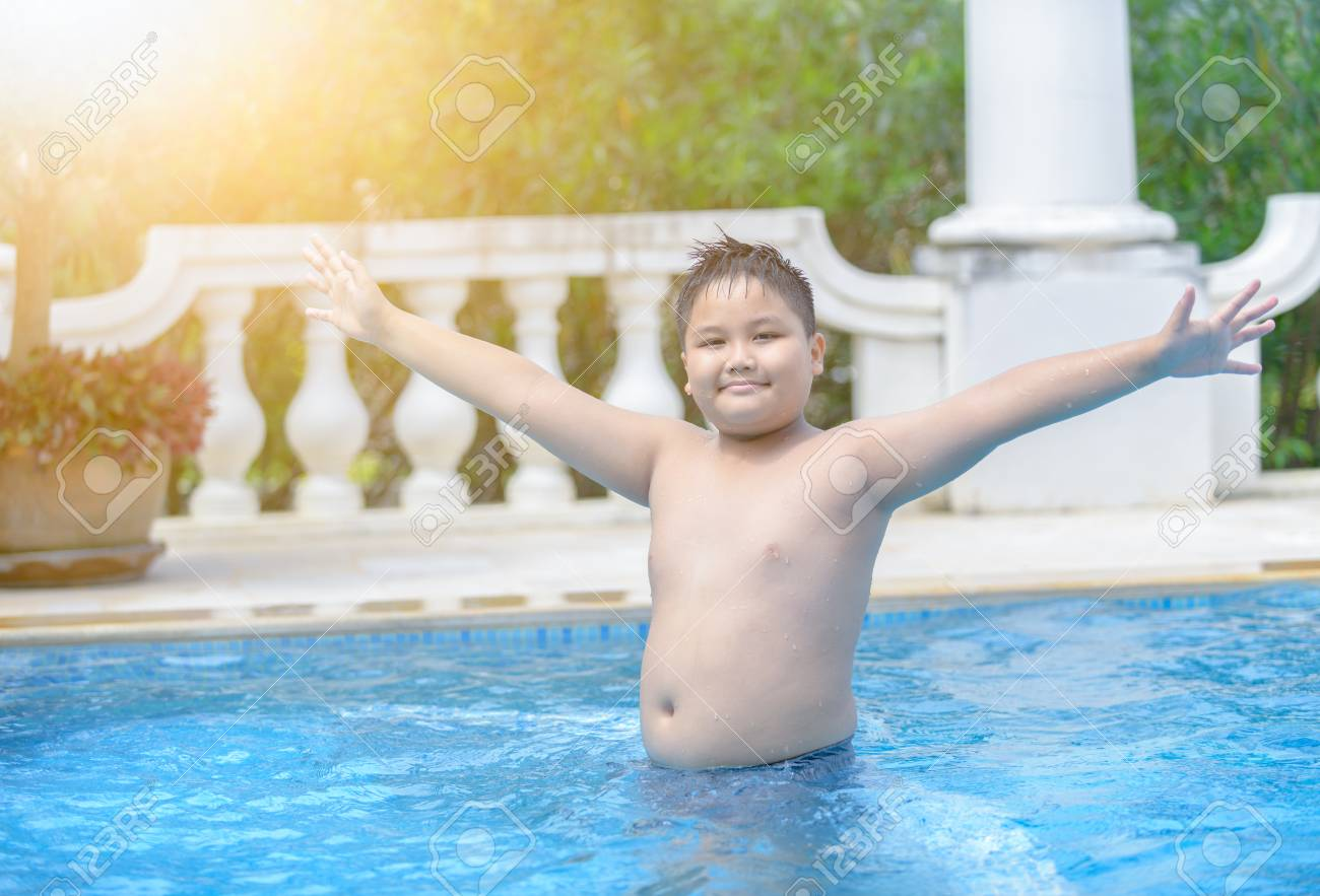 Happy obese fat boy in swimming pool, concept diet and exercise.
