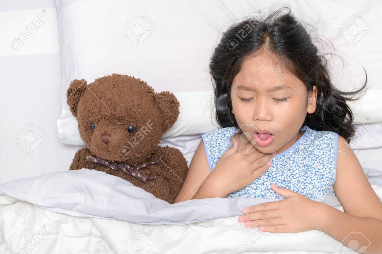 Little girl is coughing and sore throat lying on bed with toy bear, Health care concept.. - 130744018