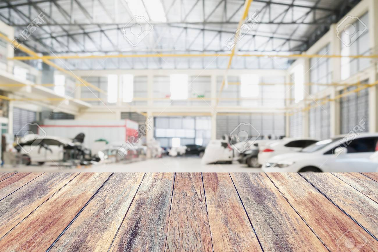 Stock Photo   Wood Table Top With Car Repair Service Centre Interior  Blurred Background. For Create Montage Auto Product Display.