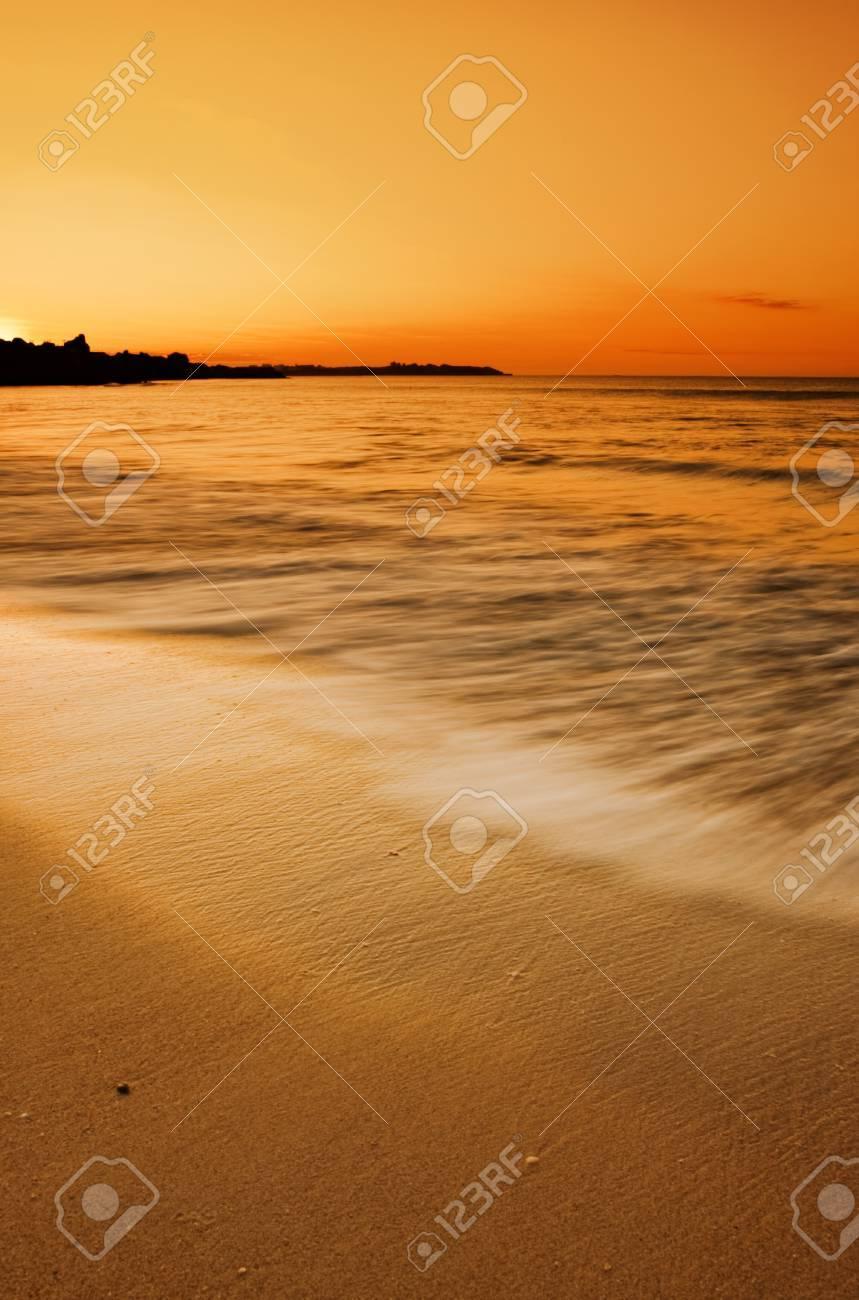 Golden sunset over motion blurred waves splashing on the sand Stock Photo - 9544931