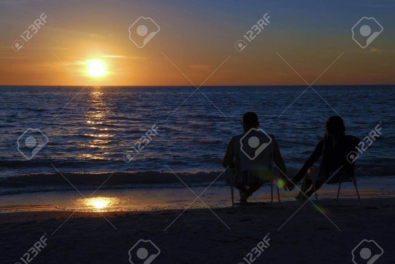 Couple Sitting On A Beach Chairs At Sunset Stock Photo Picture