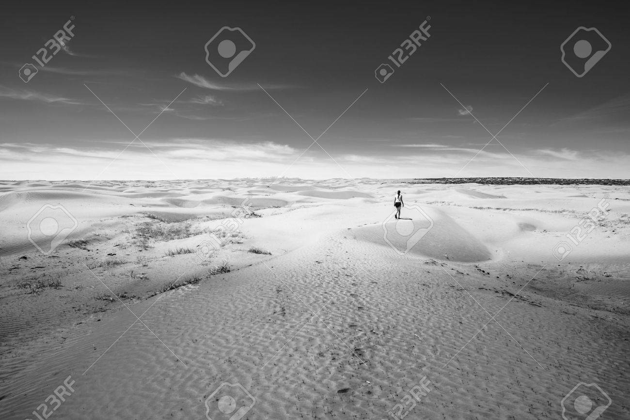 Woman walking on the desert black and white photo