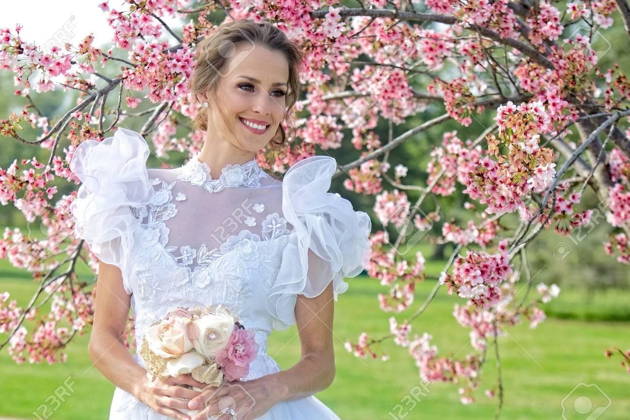 Entouré Fleurs Printemps Sur Ensoleillée Avec Jeune Cerisier En Mariée De Bouffantes Une Est Journée Robe Blanche Manches j4Ac35LqSR