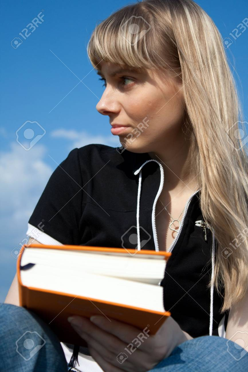 girl standing with book outdoor with sky in background Stock Photo - 5157373