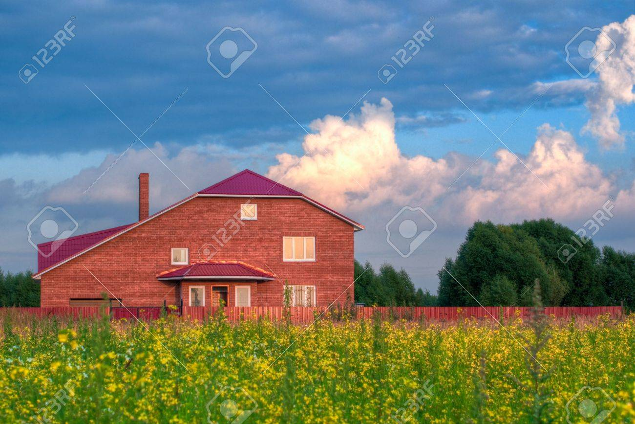 red brick house in the field of yellow flowers with cloudy sky in background Stock Photo - 5576784