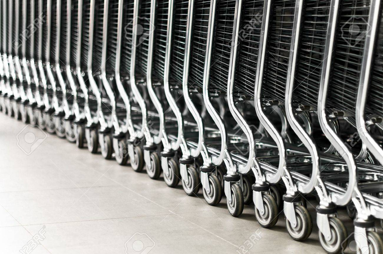 row of empty shopping carts in the big supermarket (extremely shallow depth of field, focus on fourth wheel from right) Stock Photo - 7294966