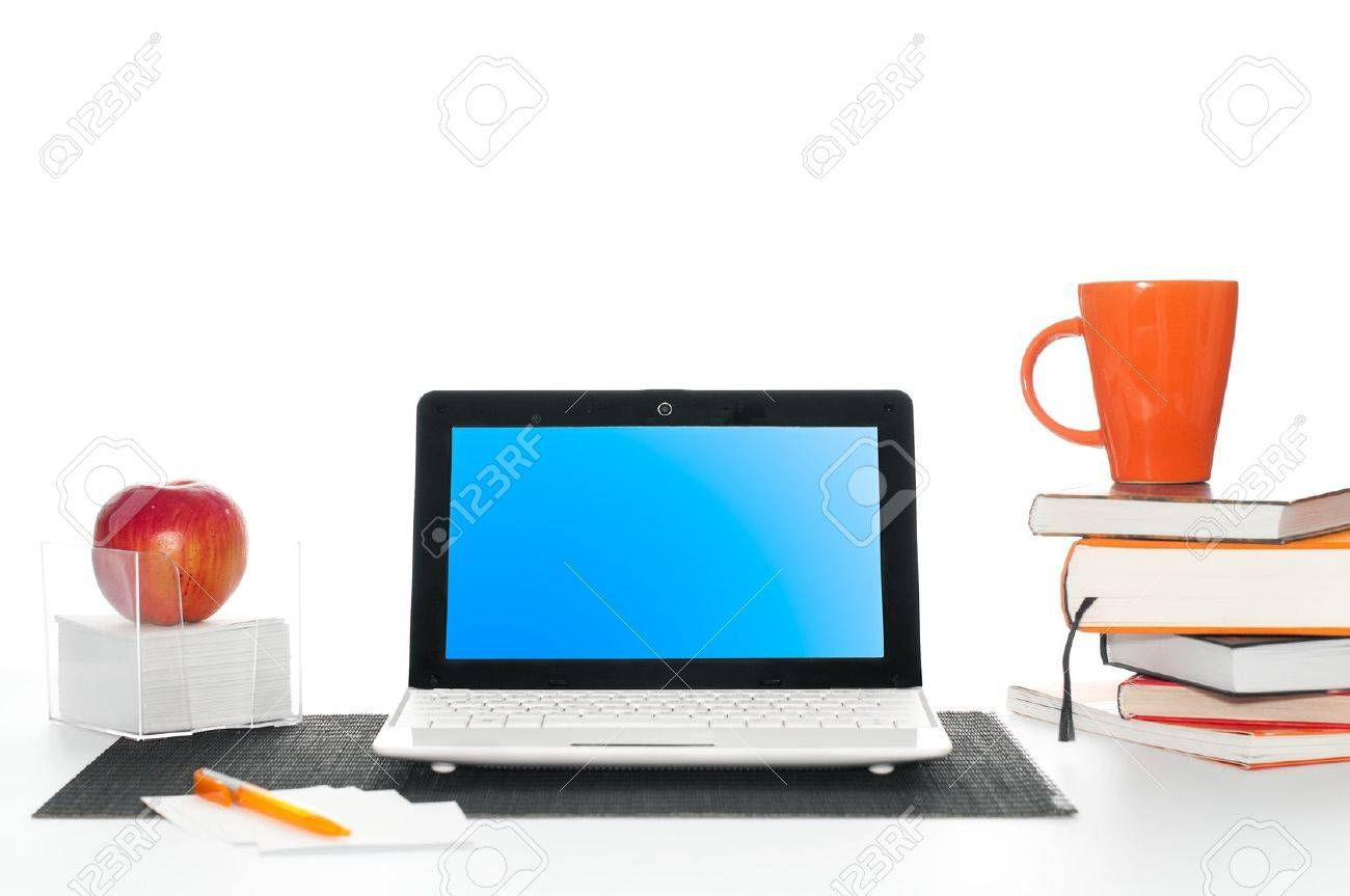office work desk with laptop computer, pile of books, cup of