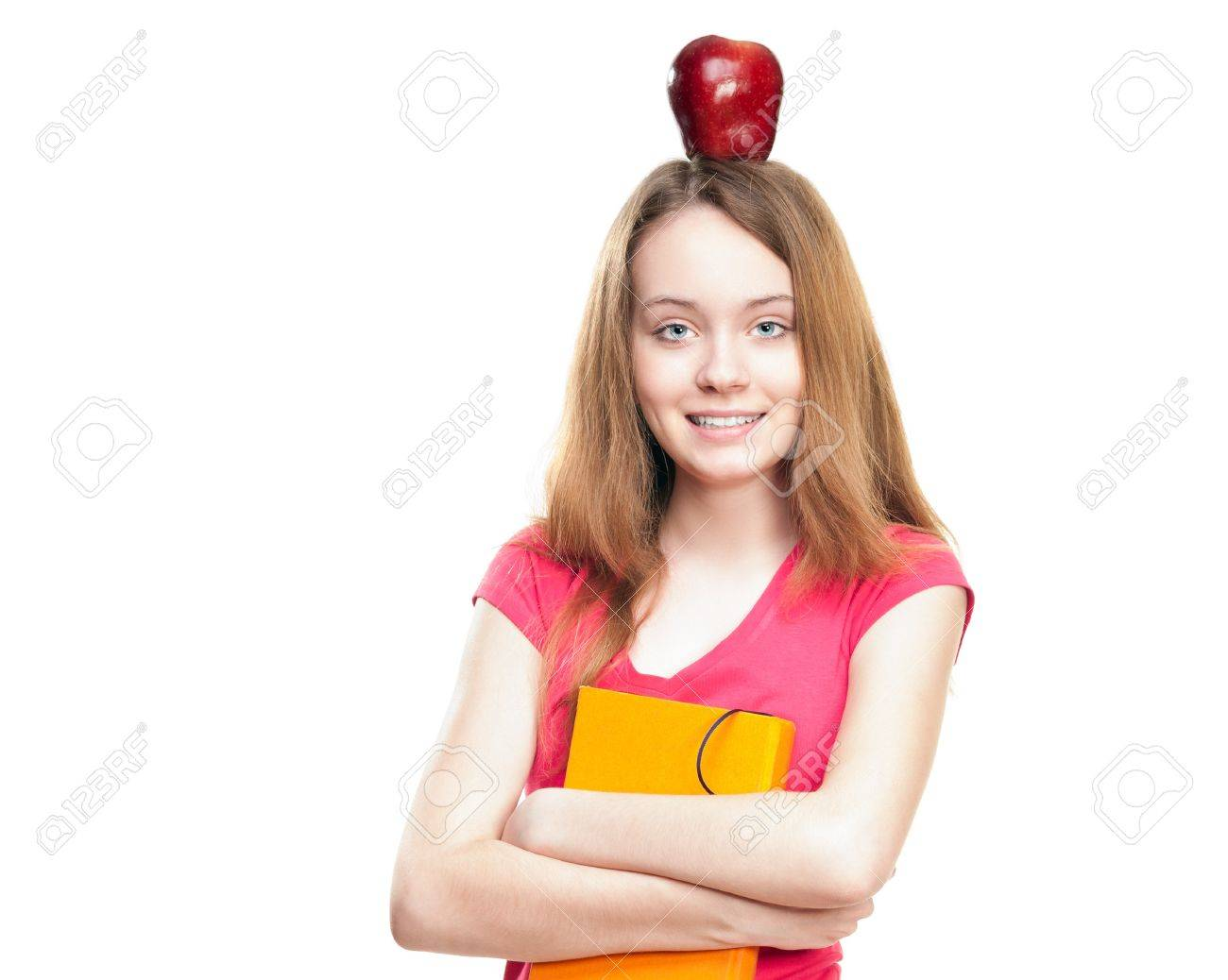 Beautiful and happy young student girl with apple on her head and book in her hands. Stock Photo - 14821809