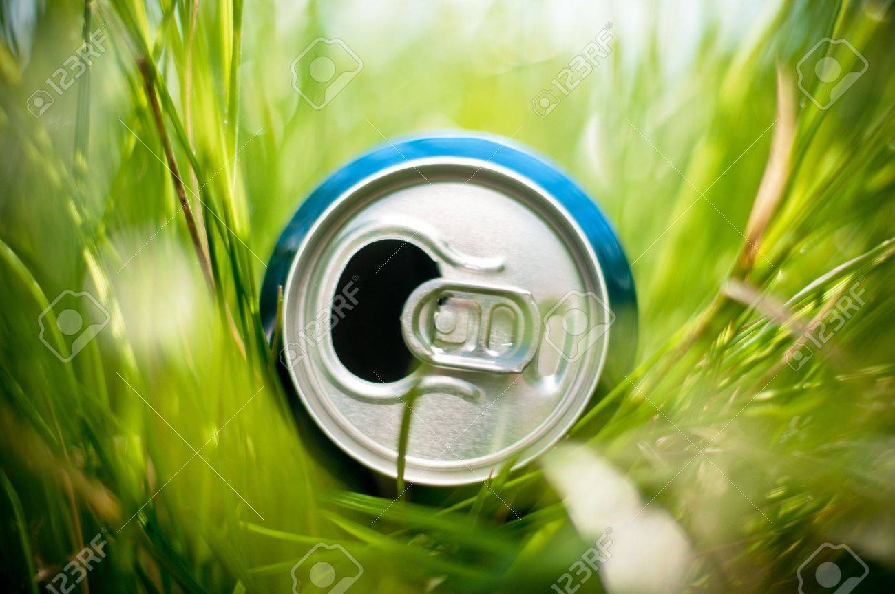 opened blue aluminum can (bottle) laying in green grass, very shallow depth of field Stock Photo - 14859754