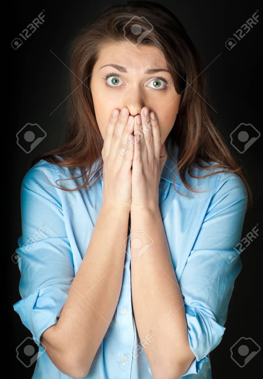 Schöne und schockierte junge Frau. Probleme oder schlechte Nachrichten.  Hände auf ihr Gesicht. Blick in die Kamera, dunklen Hintergrund.