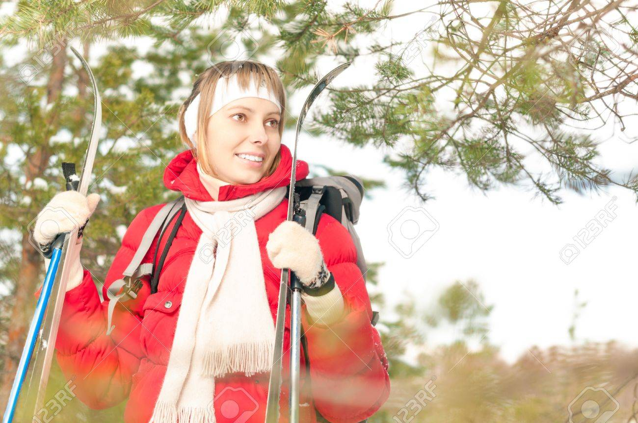 Beautiful girl in red jacket standing with backpack and ski poles  Happy smiling woman enjoys bright winter day  Winter snowy forest in background  Active sport and outdoor activity Stock Photo - 17414467