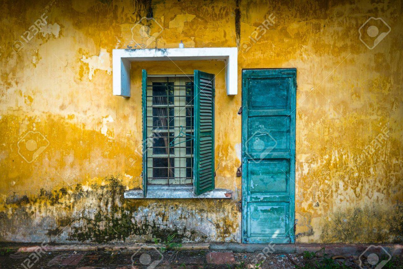 Outside view of deserted house with details in Vietnam  Old and grungy yellow wall with window and worn blue door  Abandoned place with lock on door, half-open sun blinds and metal grating on window Stock Photo - 18427244