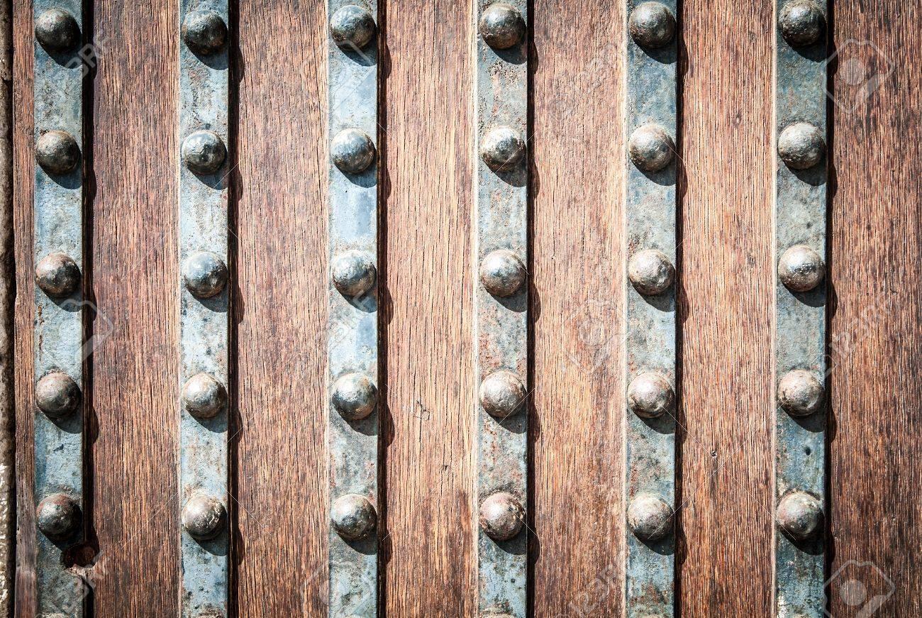 detail of old solid door. striped wood and metal door with