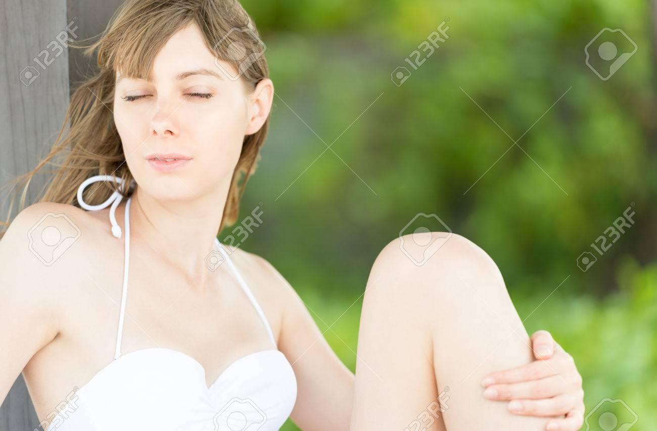 2ba7d04f49a7 Joven mujer sexy en traje de baño blanco relajante. Niña bonita sentado en  la playa con su pierna se detuvo, vegetación borrosa en el fondo. ...