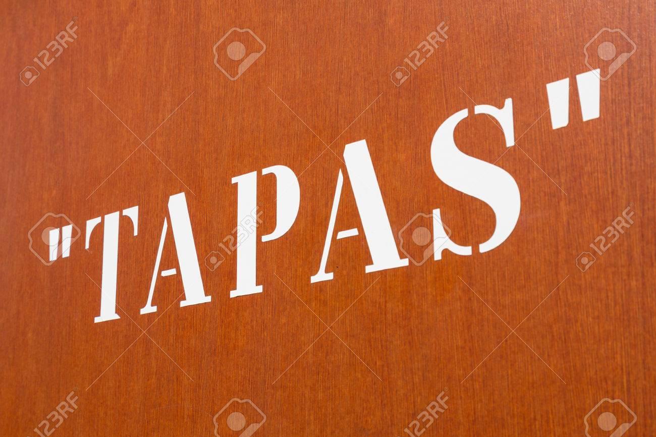 """große schablone """"tapas"""" buchstaben auf einem orangefarbenen wand"""