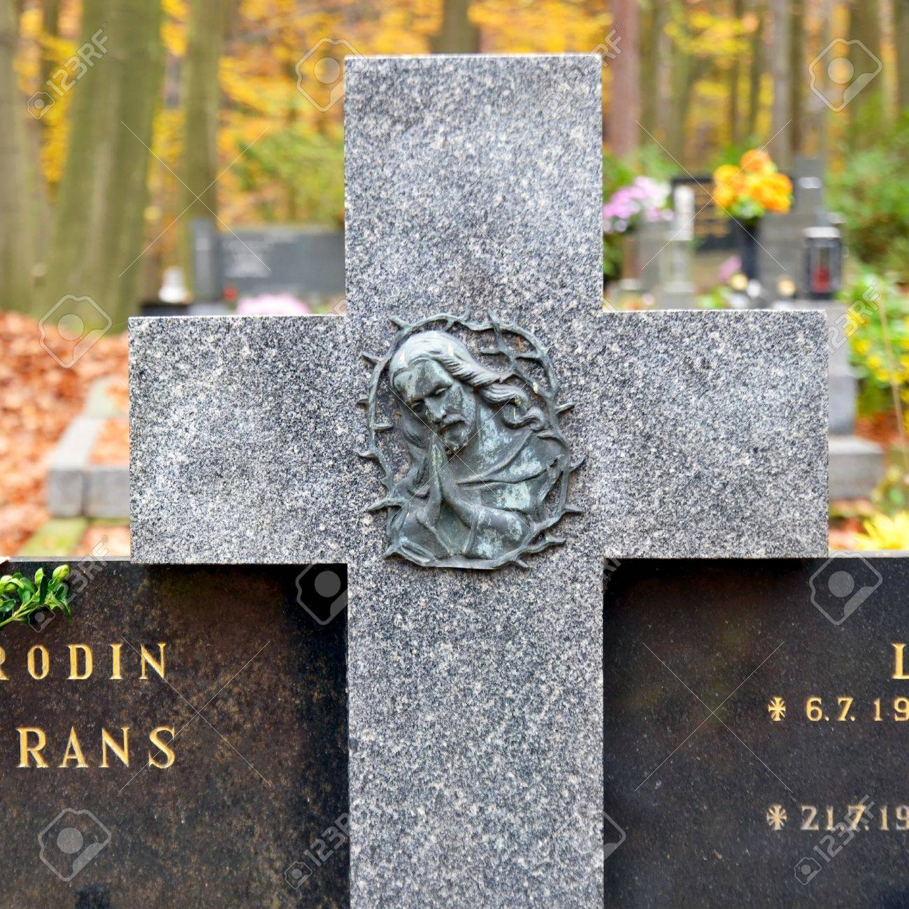 Granite cross with Jesus Christ and tombs at cemetery Stock Photo - 16268514