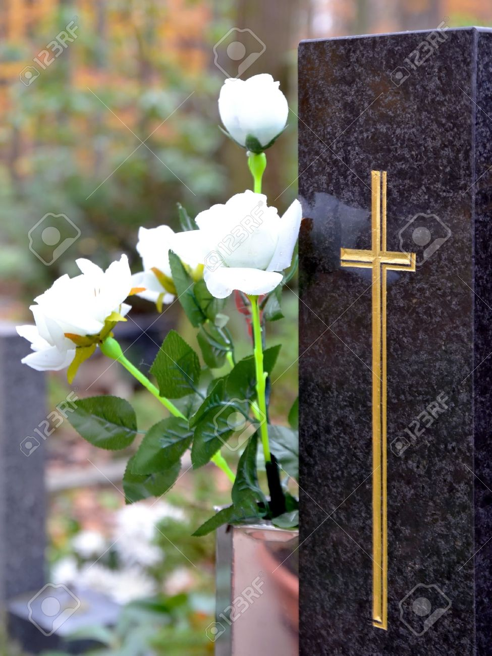 Tombstone with golden cross and white roses at cemetery Stock Photo - 16268500
