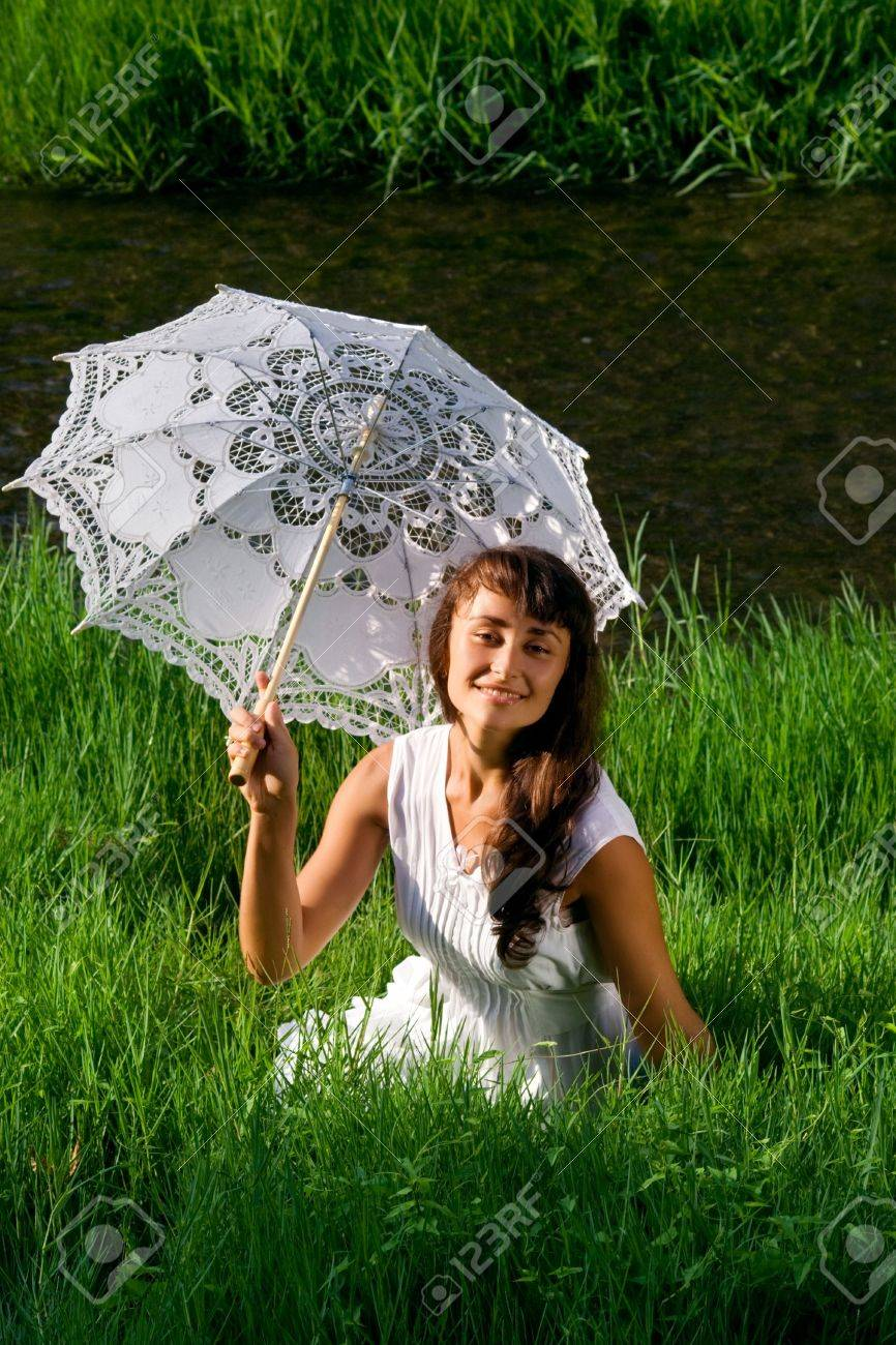 Young  attractive girl in white with sun umbrella sitting in the fresh green grass near the river Stock Photo - 7833115