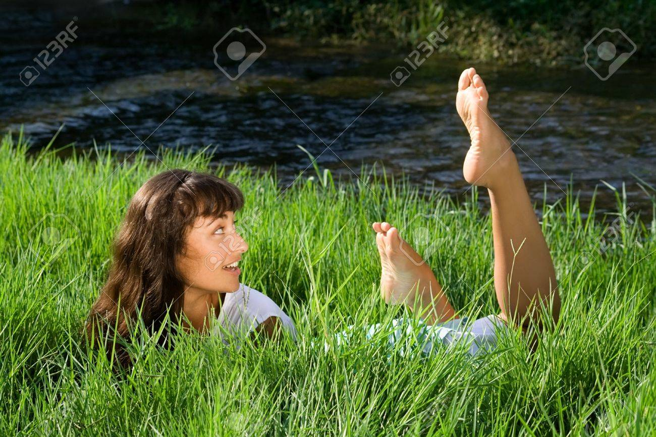 Young girl liying in the green fresh grass and looking in surprise at her feet Stock Photo - 10640669