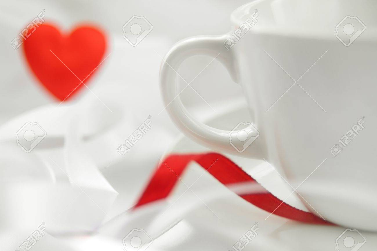 Romantic background with white cup and defocused red heart. Soft focus Stock Photo - 11303784