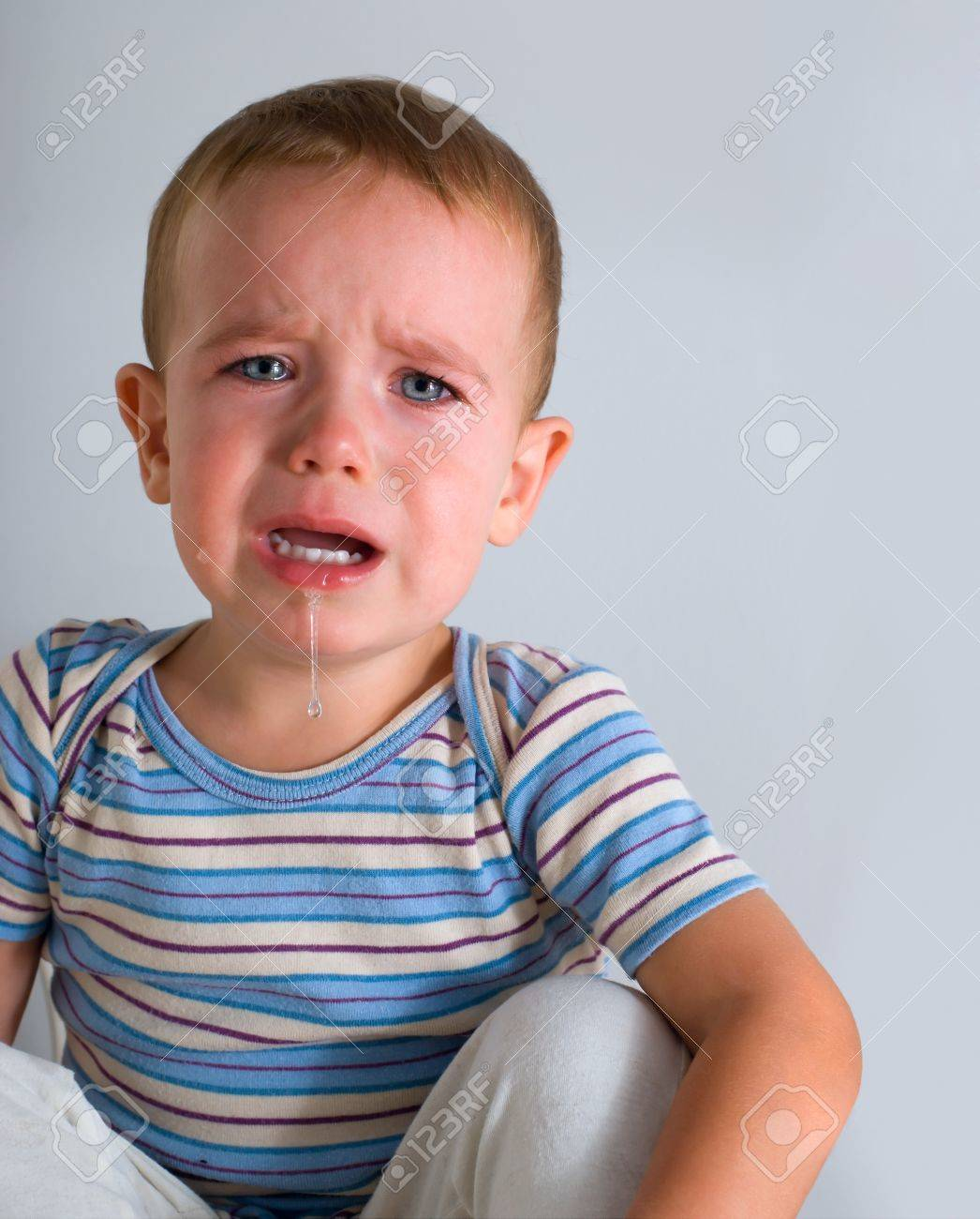 Cute crying boy on gray background Stock Photo - 10615638