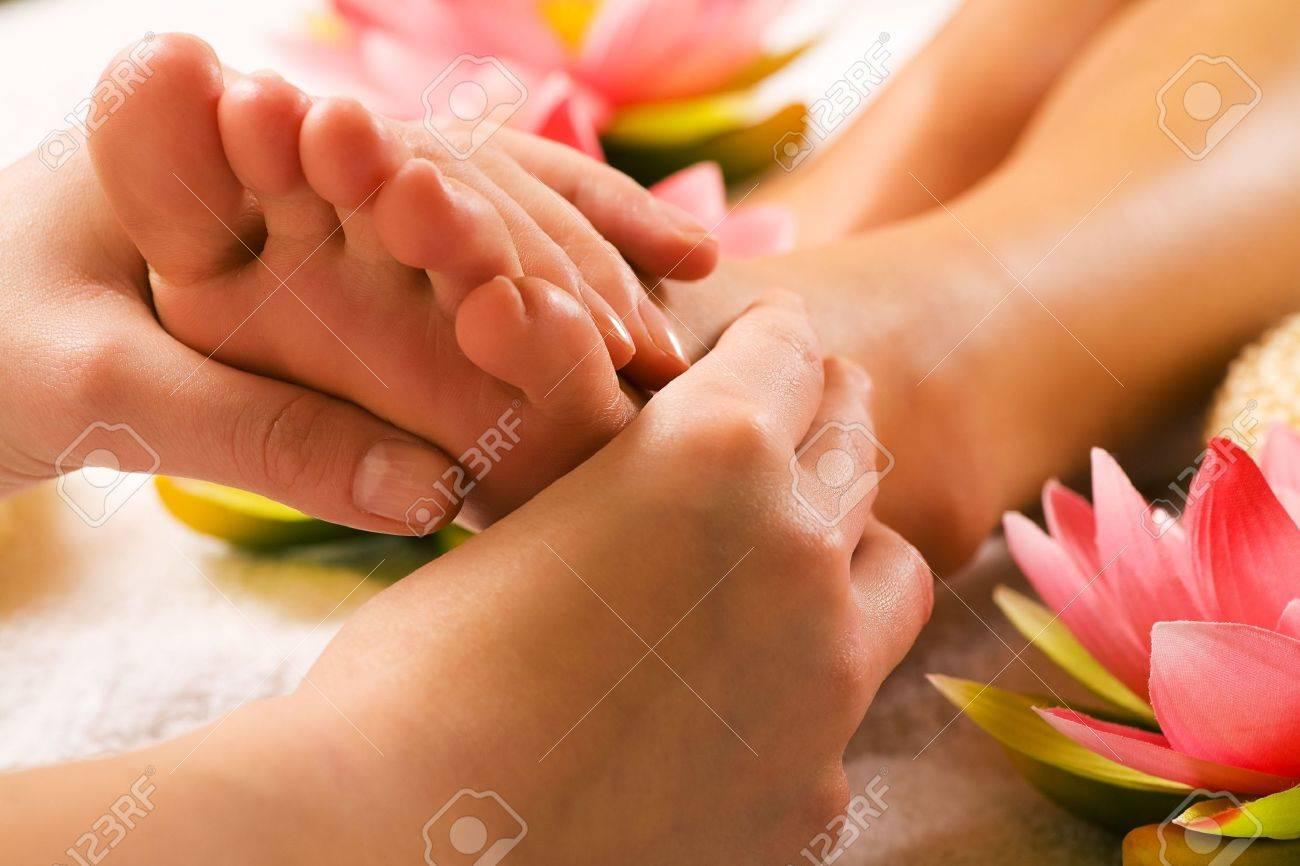 Woman enjoying a feet massage in a spa setting (close up on feet) - 3307472