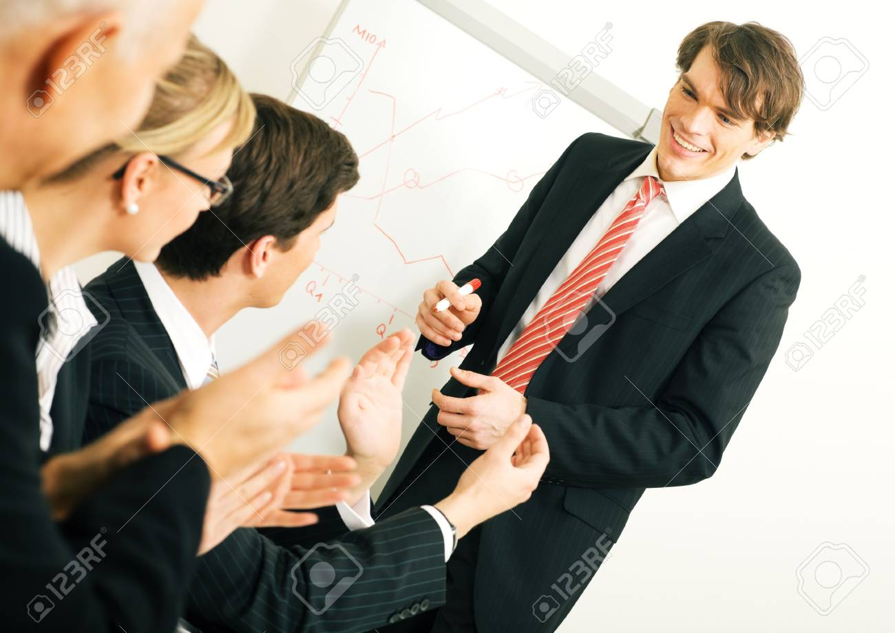 Business team applauding after a successful business presentation (selective focus only on the presenter!) Stock Photo - 3614257