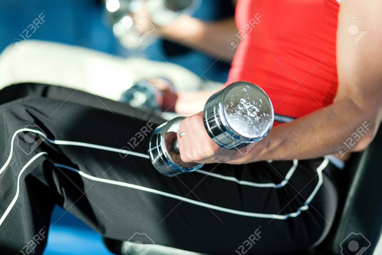 Woman lifting hand weights in a gym, in the background a man doing the same; focus on hand of woman Stock Photo - 6094157