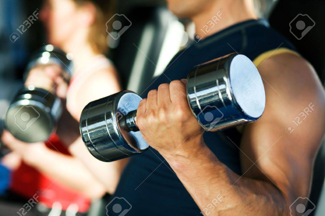 Strong man exercising with dumbbells in a gym, in the background a woman also lifting weights; focus on hand and dumbbell - 6094177