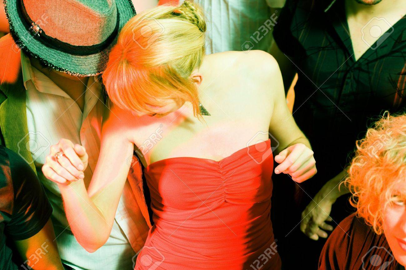 People dancing in a club, a girl in red dress in front Stock Photo - 6082018