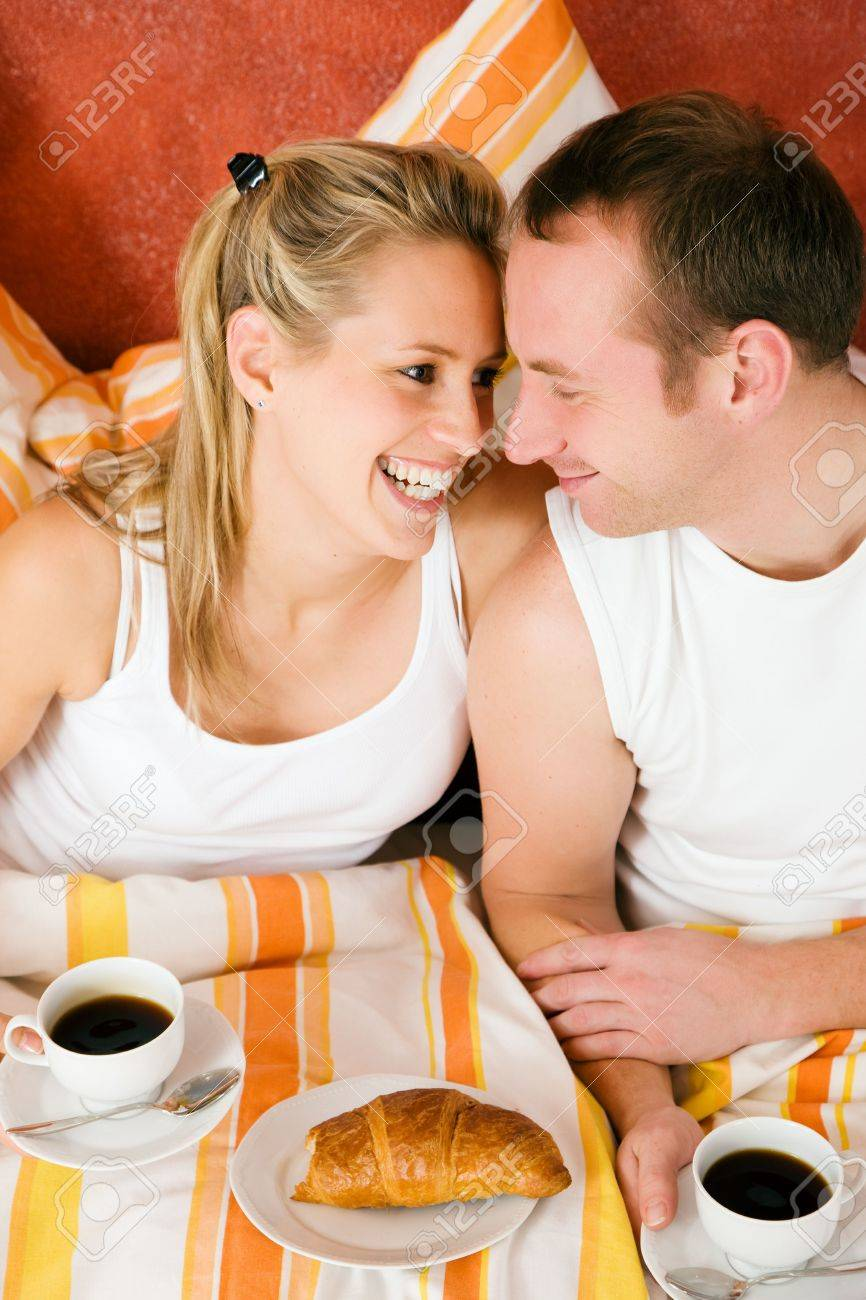 Couple having breakfast in bed in the morning looking at each other being happy and smiling Stock Photo - 6133594