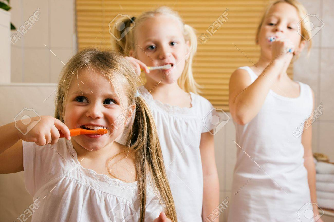 Children brushing their teeth with a hand toothbrush to get ready for bed time Stock Photo - 6140431
