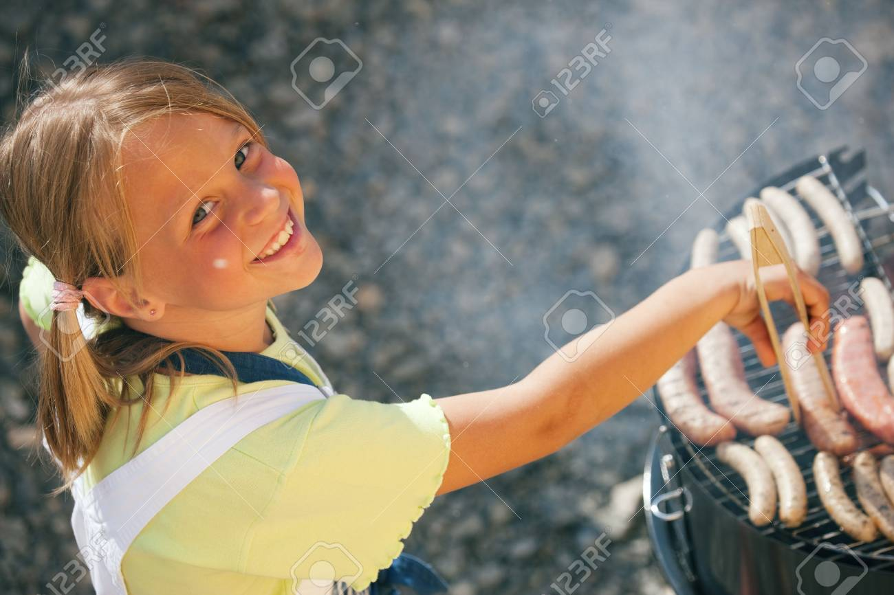 Little girl preparing meat and sausages using a barbecue grill Stock Photo - 6171461