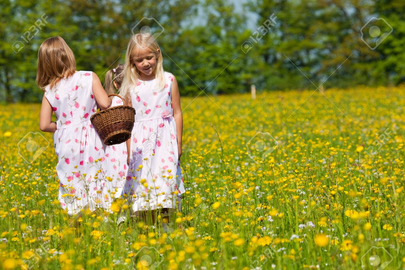 children on a beautiful sunlit meadow in spring with a basket on an easter egg hunt - Spring Pictures For Children