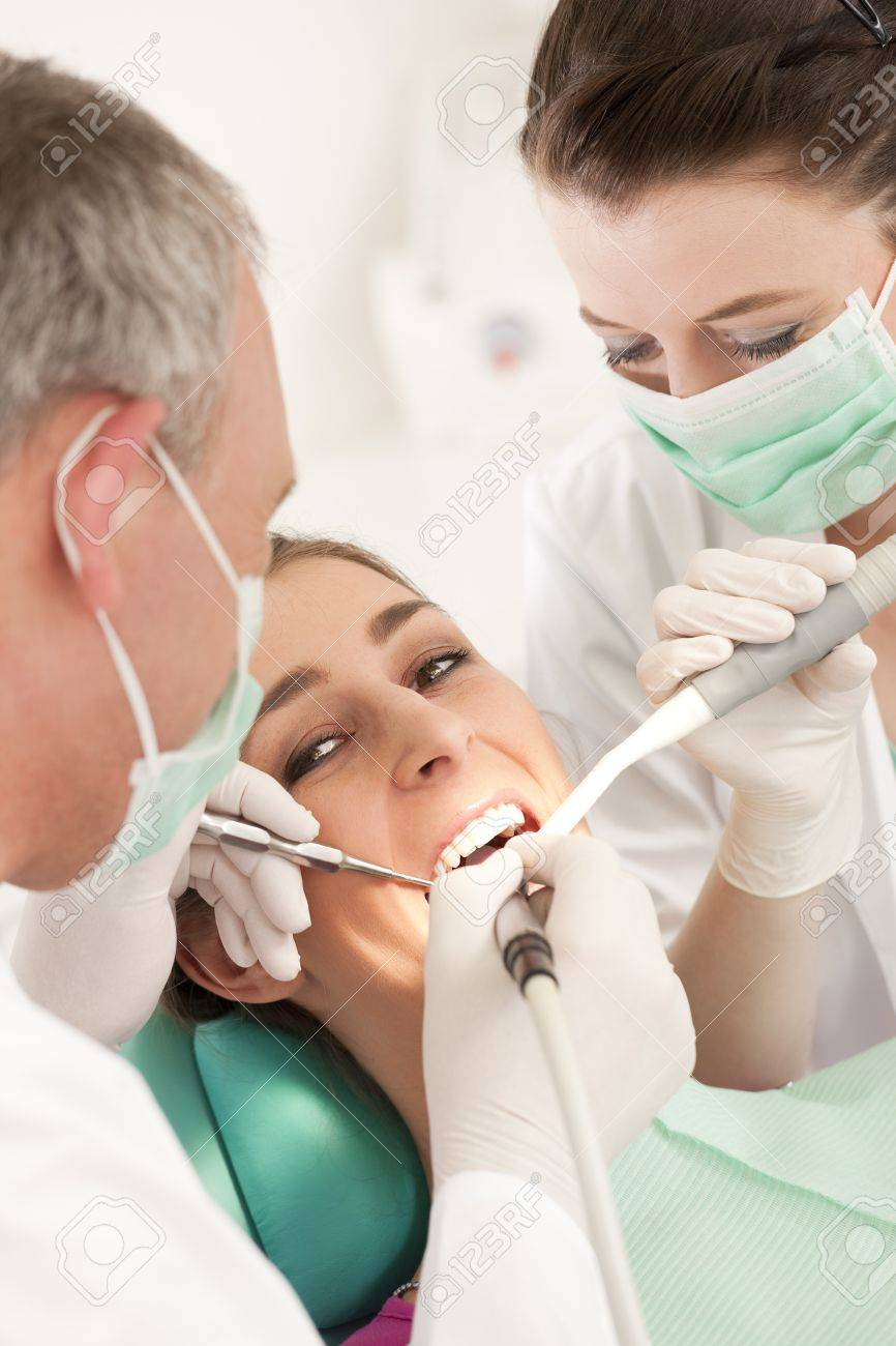 Female patient with dentist and assistant in the course of a dental treatment, wearing masks and gloves Stock Photo - 8037034