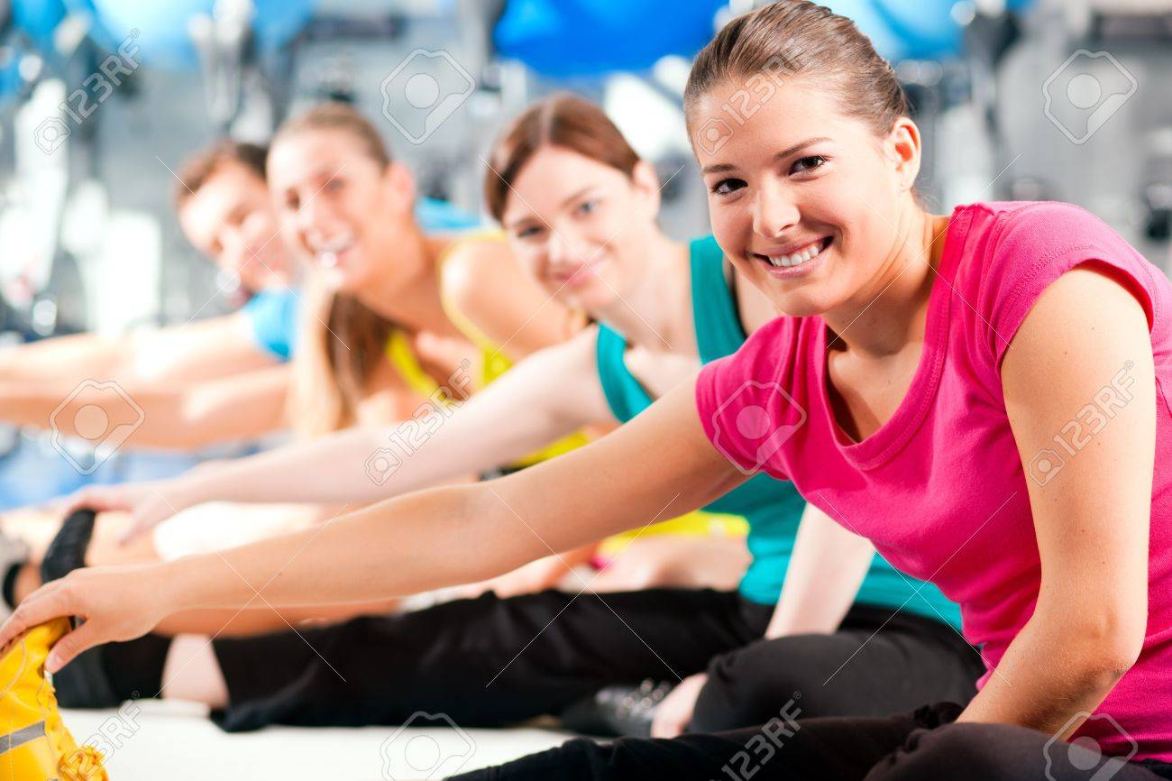 Group of four people in colorful cloths in a gym doing aerobics or warming up with gymnastics and stretching exercises Stock Photo - 8295272