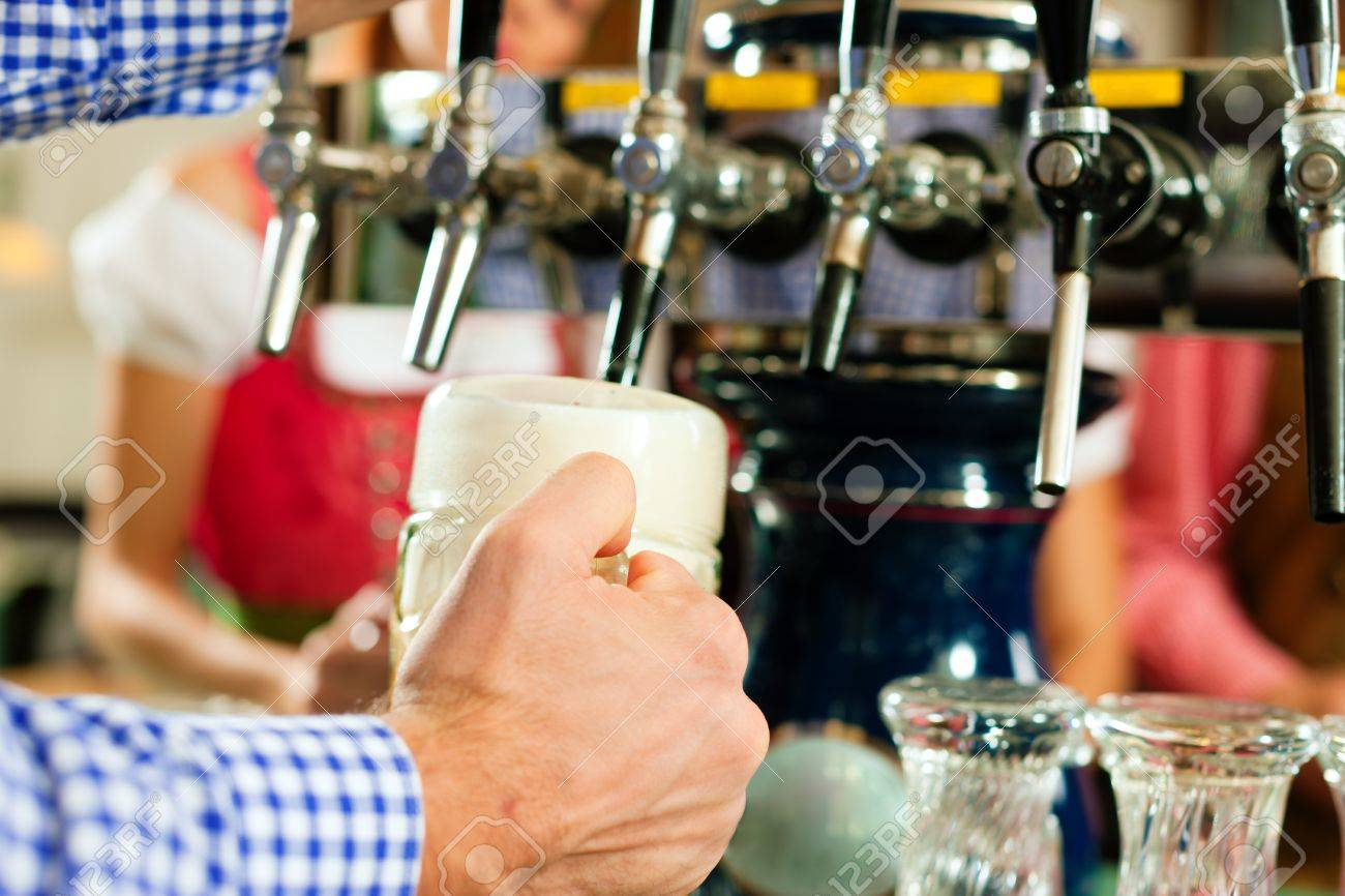 Man drawing a beer from tap on a kegerator in pub or inn, people in Bavarian Tracht are standing in the background Stock Photo - 8295276