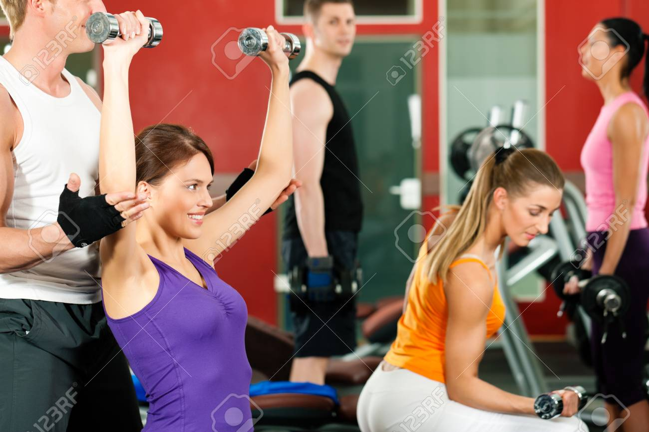 People in gym exercising with weights Stock Photo - 9415515
