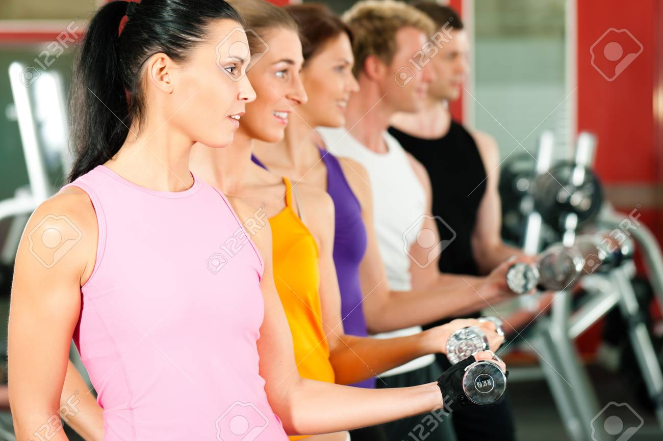 People in gym exercising with dumbbells Stock Photo - 9415531