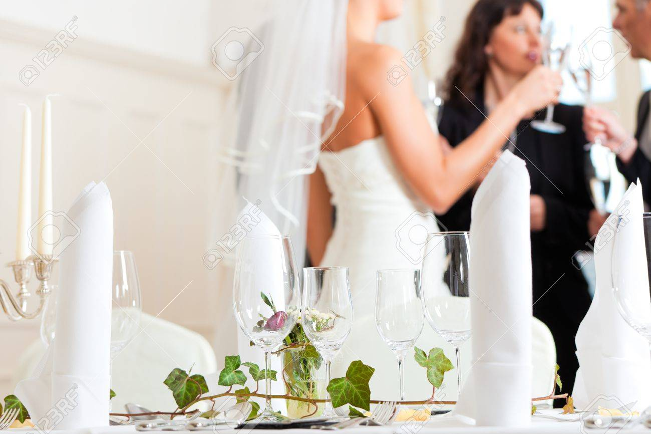 Wedding table at a wedding feast decorated with flowers - in the background the bride Stock Photo - 9844605