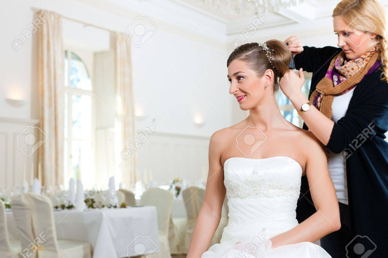 stylist pinning up a brides hairstyle before the wedding stock photo 9860583